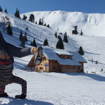 Zu sehen ist eine winterliche Landschaft mit Skipiste. Der Blogautor macht einen Kopfstand