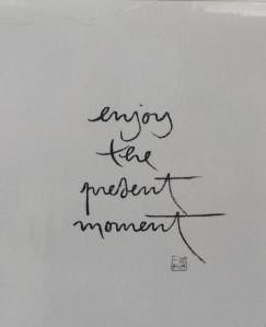 """Das Bild ist ein Photo eines Spruchs. Er lautet """"Enjoy the present moment"""""""