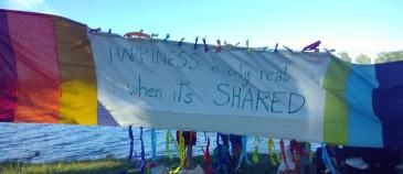 """Das Bild zeigt ein Transparent das zwischen Bäumen vor der Neuen Donau aufgehängt ist. Darauf steht: """"Happiness is only real when it's shared"""""""