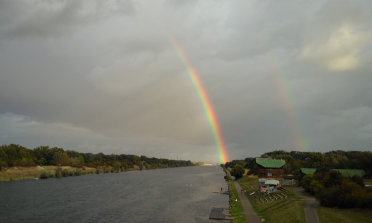 Das Bild zeigt einen dicken Regenbogen über der Neuen Donau in Wien