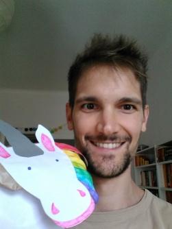 Das Bild zeigt den Blogautor Lukas. Er lächelt in die Kamera und hält eine Papierhandpuppe in der Hand
