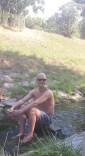 Das Bild zeigt den Autor. Er hat eine Glatze von der Chemtherapie und sitzt auf einem Stein in einem kleinen Bach an einem heißen Sommertag