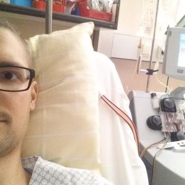 Das Bild zeigt den Autor, auf einem Bett im Spital. Es steht ihm zwei Schläche aus dem Hals.Es wird Blut in einem Zellseperator gereinigt