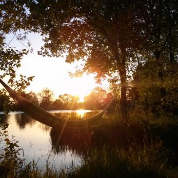 Auf dem Bild ist eine Hängematte vor einem ruhigen See zu sehen. Die Sonne geht gerade unter und taucht den Himmel in orang-gelbes Licht.