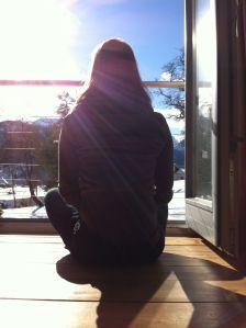 Wir sehen eine Person von hinten die bei offener Balkontüre sitzt und auf eine schneebedeckte Winterlandschaft blickt
