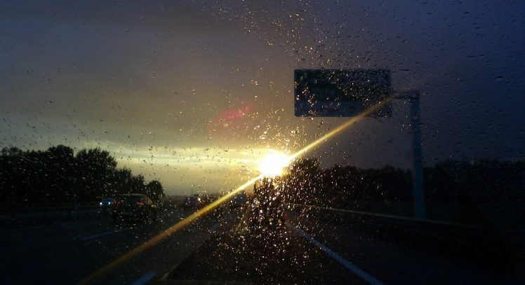 Bild zeigt einen Sonnenuntergang nach Regen. Es ist aus einem Auto auf der Autobahn hinaus fotographiert durch die verregnete Scheibe hindurch