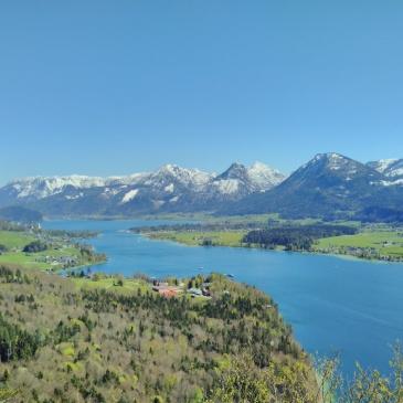 Das Bild zeigt den Wolfgangsee im Salzkammergut mit Schnee bedeckten Gipfeln im Hintergrund an einem sonnigen Frühlingstag