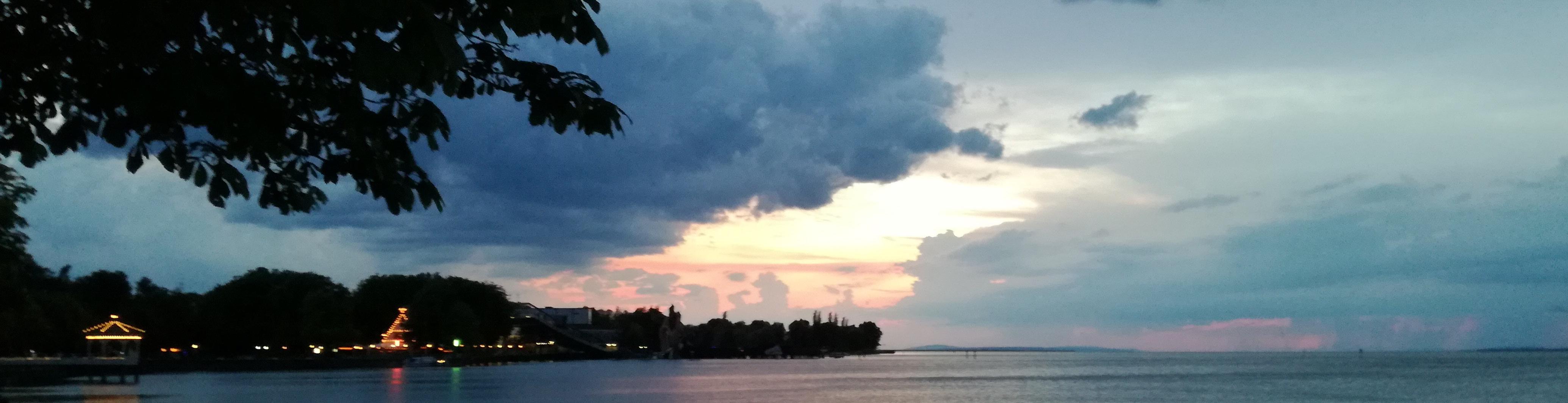 Bild zeigt einen See mit rosa-gelben Himmel bei untergehender Sonne