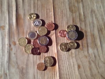 Das Bild zeigt ein paar Münzen auf einem Holztisch