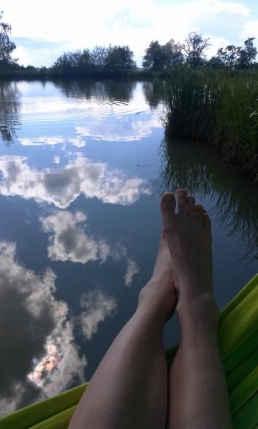 Bild zeigt Füße die über eine Hängematte hängen. Im Hintergrund ist ein See in dem sich Wolken spiegeln
