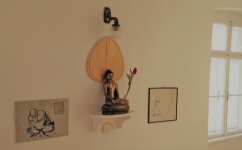 Bild zeigt einen kleine Buddhastatue und zwei Zeichnungen an einer Hauswand