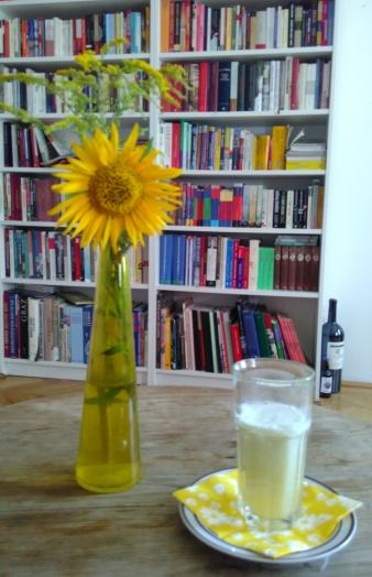 Bild zeigt einen Tisch mit einem Glas frisch gepresstem Gemüse-Obst-Saft und einer Sonnenblume
