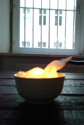 Bild zeigt eine brennende Kerzenschale auf einem Holztisch
