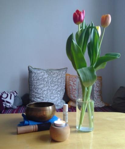 Bild zeigt Tisch mit Tulpen,Klangschale,einem Duftöl und Kerze