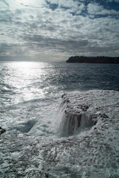 Bild zeigt das Meer,welches sich an einer Brandung schäumt und bricht