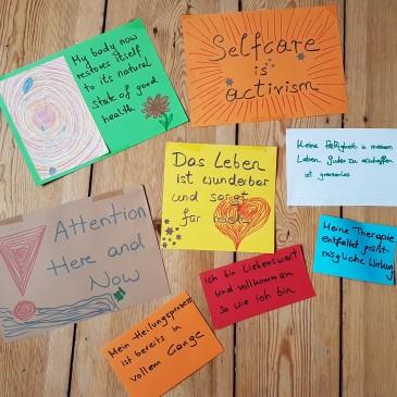 Das BIld zeigt bunte Zettel oder Schilder, auf denen Affirmationen stehen