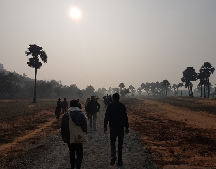 Bild zeigt einen staubigen Weg mit roter Erde und Palmen und eine Gruppe von Menschen,die darauf entlang geht.