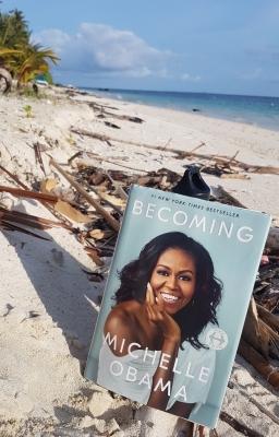 """Bild zeigt einen Sandstrand mit dem Buch """"Becoming"""" von Michelle Obama"""