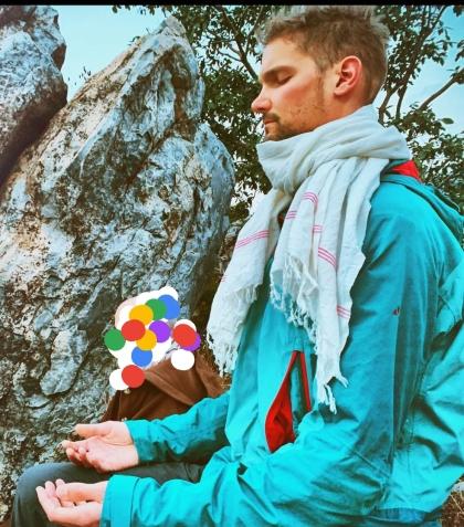 Der Autor sitzt meditierend vor einem Felsen