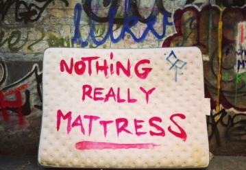 """Bild zeigt eine Matratze, die an einer Wand mit Graphitti angelehnt ist. Darauf steht """"Nothing really mattress"""""""