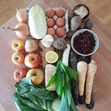 Bild zeigt Obst und Gemüse, die auf einer Holzplatte angerichtet sind