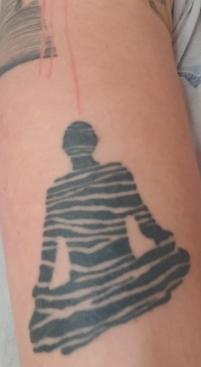 Bild zeigt ein Tattoo einer meditierenden Figur. Die Figur ist aus einer schwarz-weißen Blattstruktur ausgeschnitten