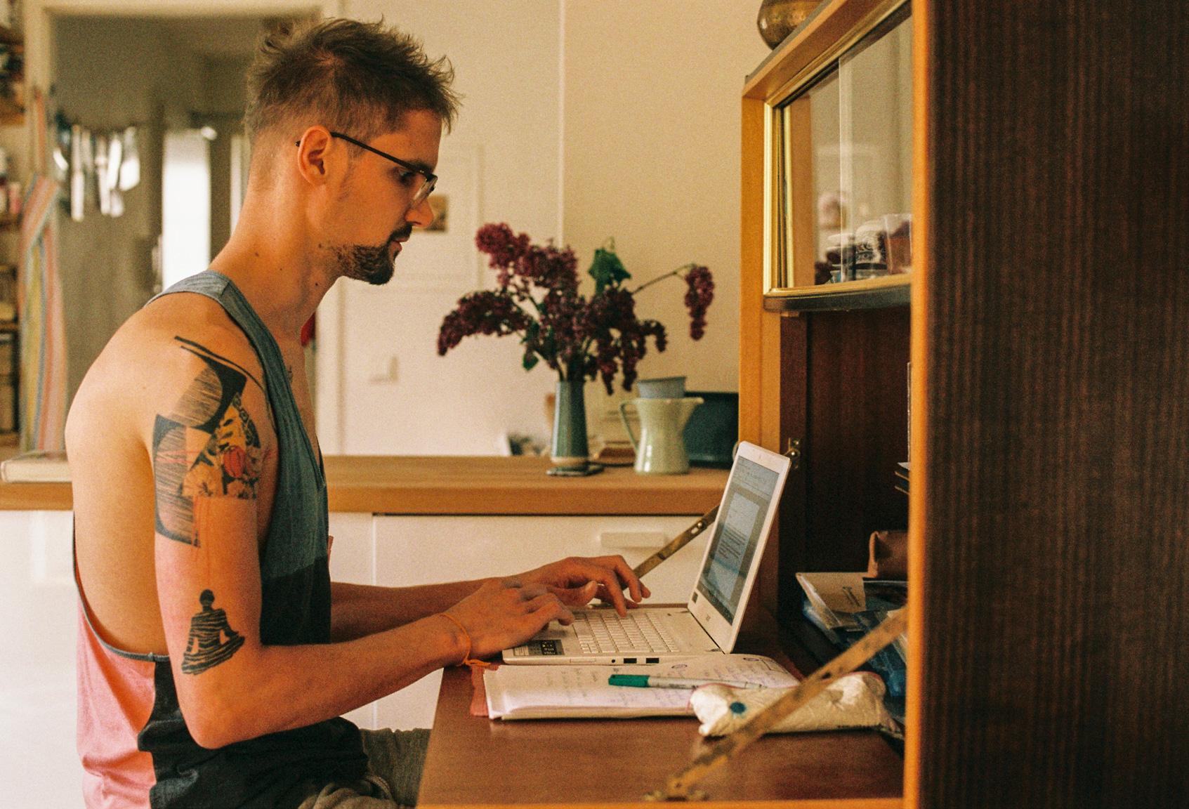 Bild zeigt mich beim Schreiben am Computer auf meinem Arbeitsoplatz. Im HIntergrund steht ein Flieder und das Licht ist goldig-gelb.