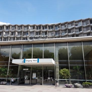 das Bild zeigt den Eingang zum Benjamin-Frankling-Campus der Charité Berlin. Der Himmel ist blau